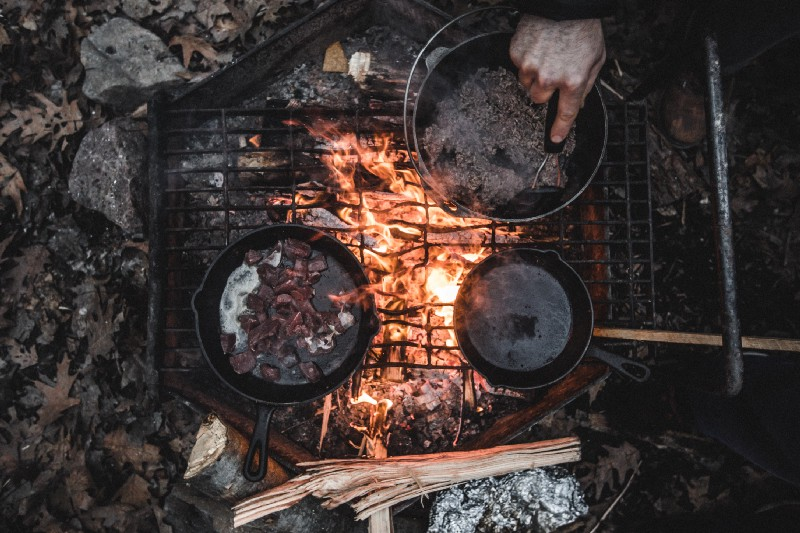 """Two cast iron pans and a pot of water over an outdoor fire-lit stove outdoors with a hand mixing the water"" by Teddy Kelley on Unsplash"